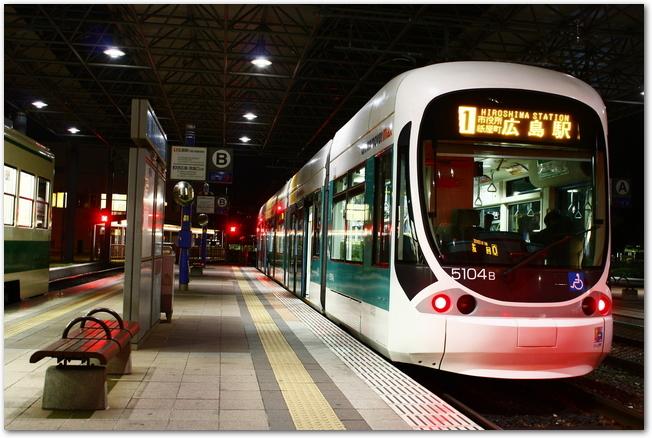 広島電鉄路面電車が夜のホームに停車している様子