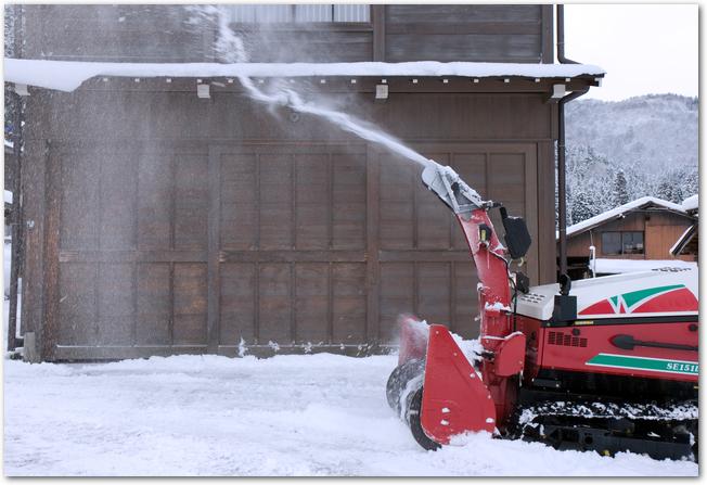 雪の中作業をするショベルカー
