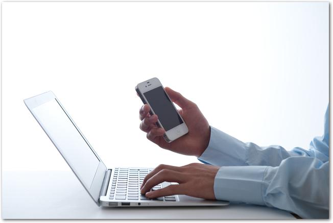 ノートパソコンとスマートフォンを操作する人