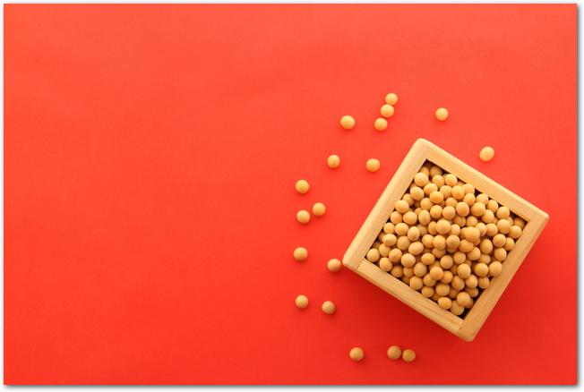 赤い背景に豆まきの豆が置いてある様子