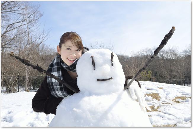 雪だるまの周りにいる笑顔の大学生たち