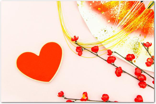 赤いハート型の絵馬と梅と扇子