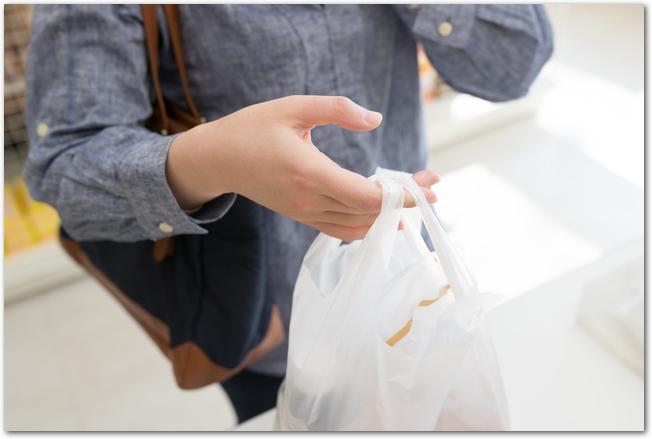 スーパーのビニール袋を持って道を歩く女性