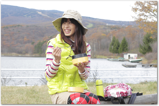 屋外でお弁当を食べている女性の様子