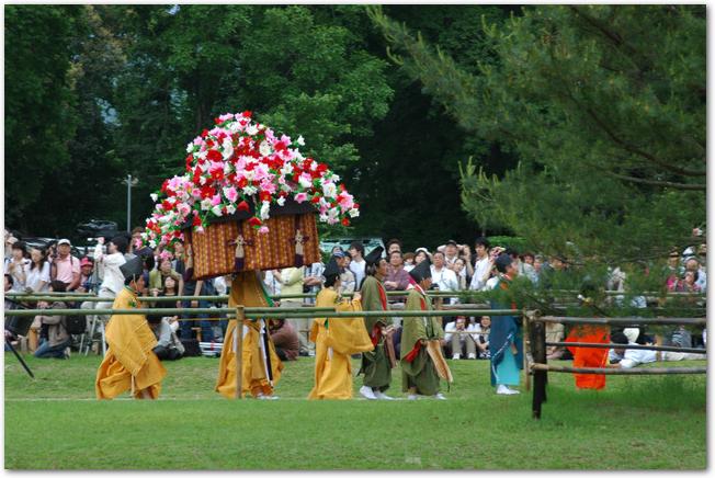 葵祭の行列で花笠を持った人が通っていく様子