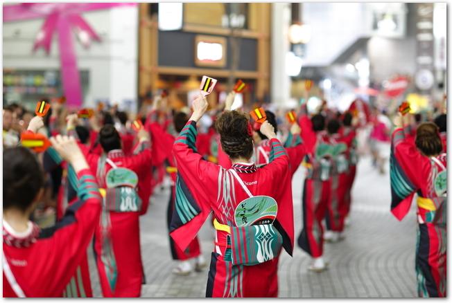 YOSAKOIソーラン祭りで鳴子を手にして踊る女性の踊り子たち