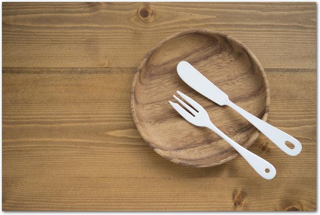 木のテーブルに置かれたお皿とカトラリー