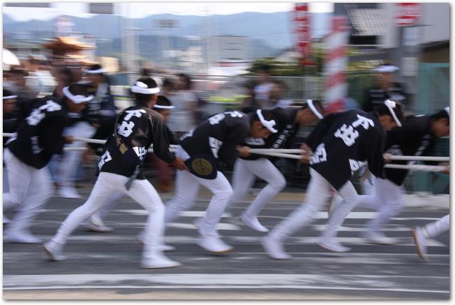 だんじりを曳きながら疾走するハッピ姿の男性たち