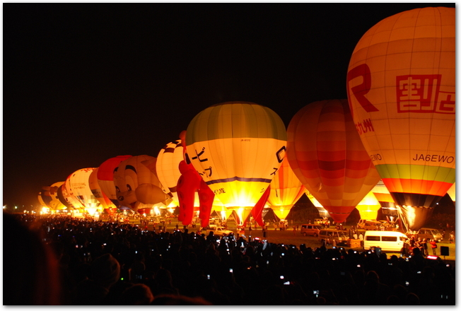 夜にライトアップされている係留中のたくさんの気球