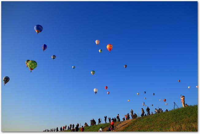 青空に上がる気球を見上げる人々のシルエット