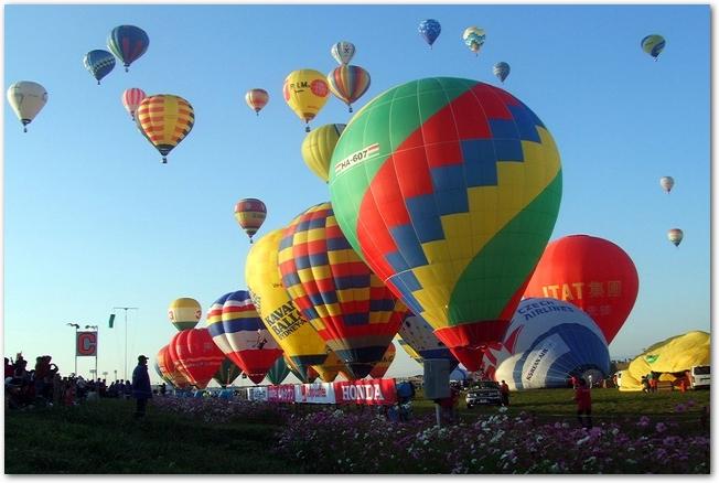 青空に次々と上がっていく色とりどりの気球