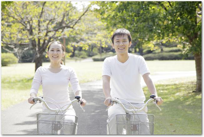 紅葉の中をサイクリングするカップル