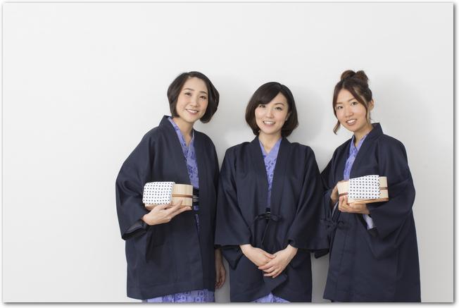宿の温泉に向かう浴衣姿の3人の女性