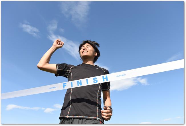 ゴールテープをきる男子マラソン選手
