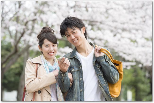 満開の桜の木の下を歩くカップルの様子