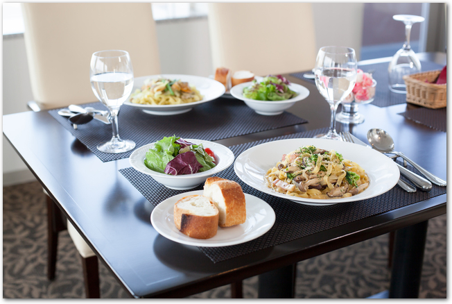 パスタなどの料理が置かれたイタリアンレストランのテーブル
