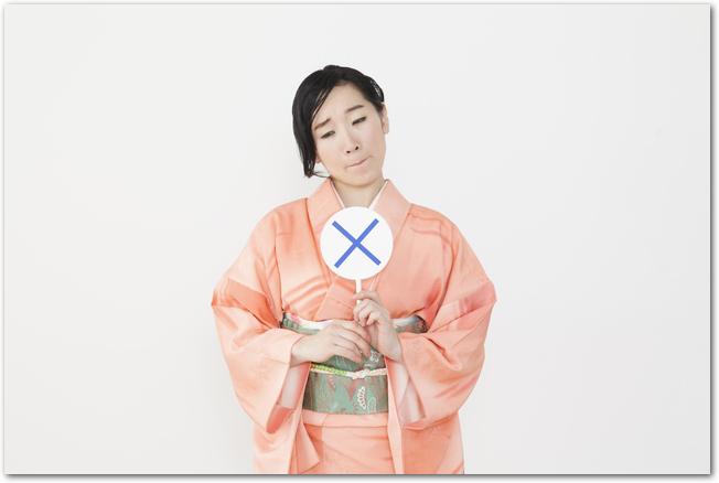 バツ印の札を出す浴衣姿の女性の様子
