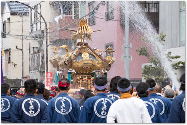 放水の水の中を練り歩く神輿と担ぎ手たちの様子