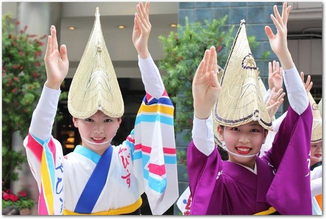 笠をかぶって阿波踊りを踊っている女性たちの様子