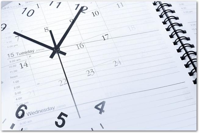 スケジュール帳の上に透けた時計の文字盤が重なっている様子
