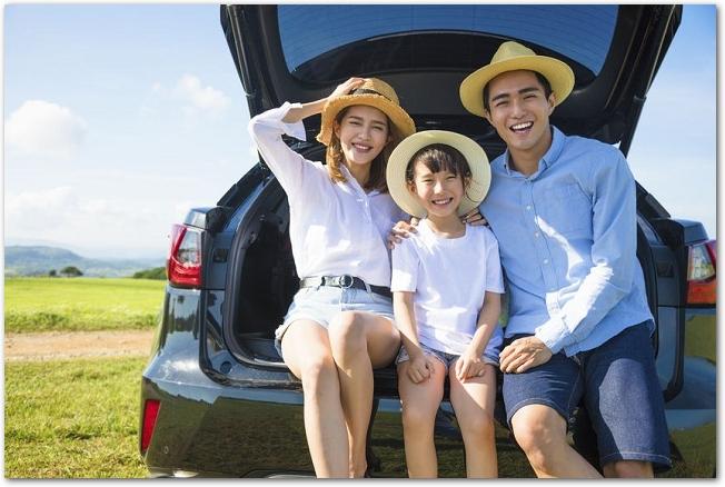 車の後ろに腰かける麦わら帽子をかぶった家族の様子