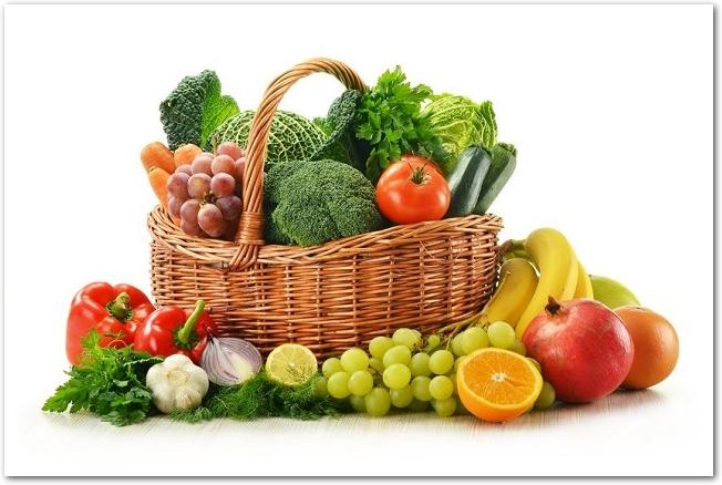 野菜が盛られた木のバスケットの周りに果物が置いてある様子