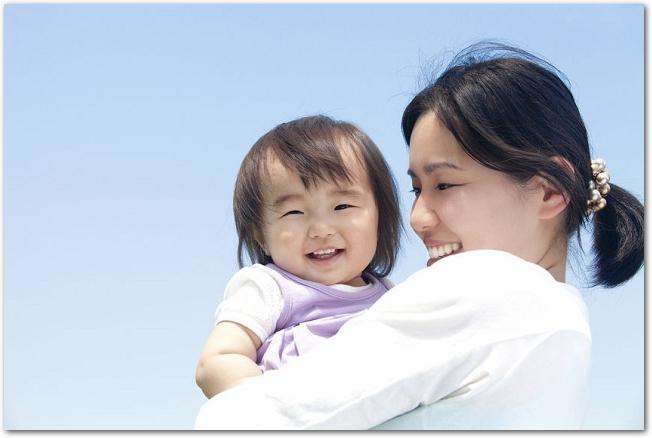 青空の下で笑顔の女の子を抱っこする母親の様子