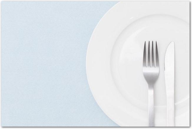 水色のテーブルクロスの上に置かれた白皿とカトラリー