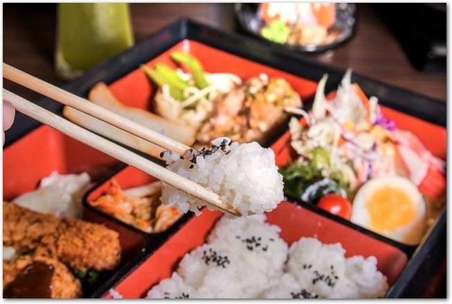 松花堂弁当のご飯を箸で持ち上げている様子
