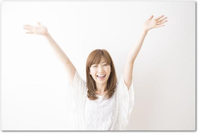 右手の拳を突き上げる笑顔の女性の様子