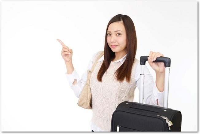 人差し指を立てるスーツケースを持った女性の様子
