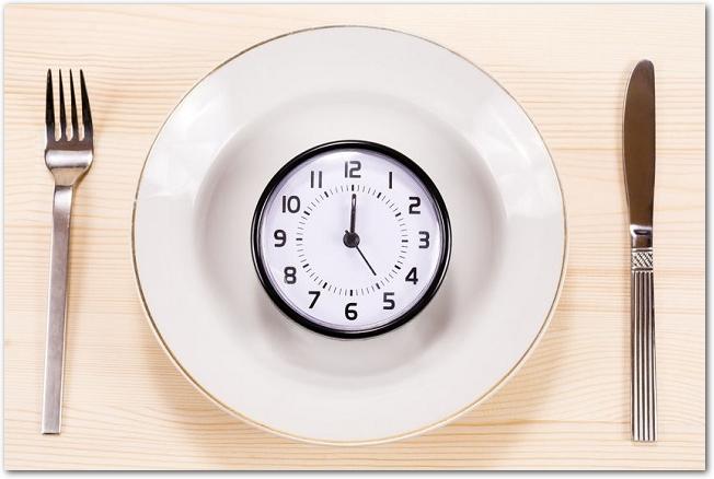 カトラリーと白いお皿の上に時計が乗っている様子
