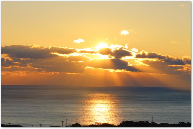 海の向こうの淡い色の空に初日の出が昇る光景