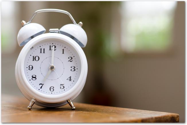 机に置かれた白い目覚まし時計