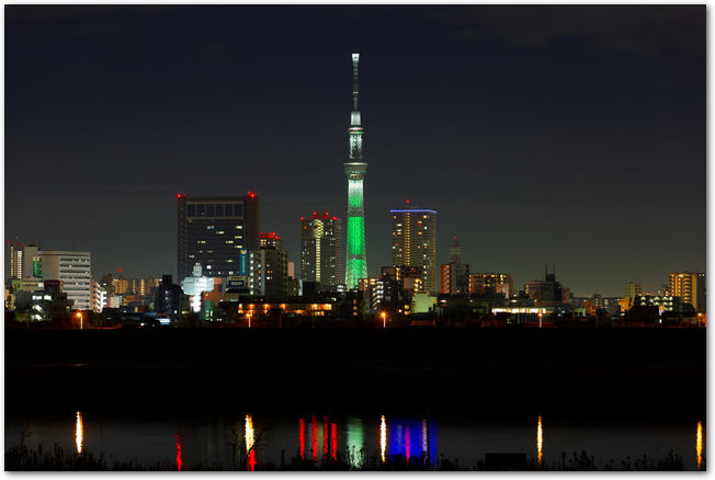 グリーンにライトアップされたスカイツリーと周辺ビルの夜景