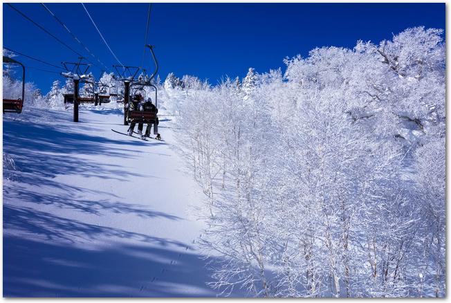 安比高原の樹氷と西森山ペアリフトに乗るスキー客