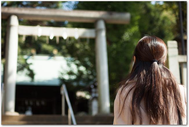 神社の鳥居を見上げる女性の後ろ姿
