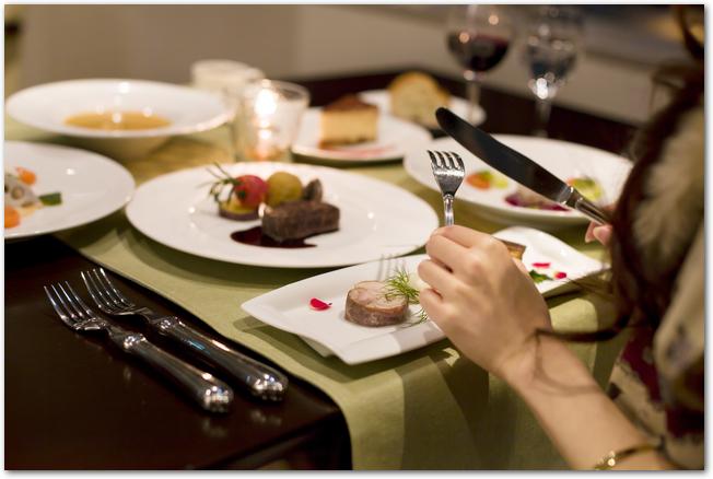 フレンチレストランでのディナーを楽しむ女性の様子