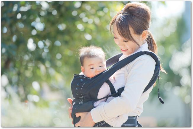 抱っこひもで赤ちゃんを抱っこしている母親の様子