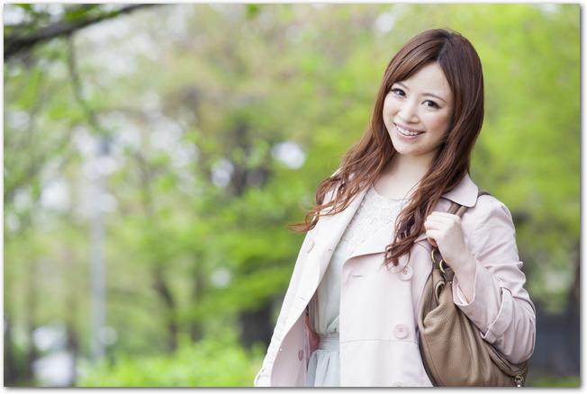 新緑の並木道を歩くトレンチコートを着た女性
