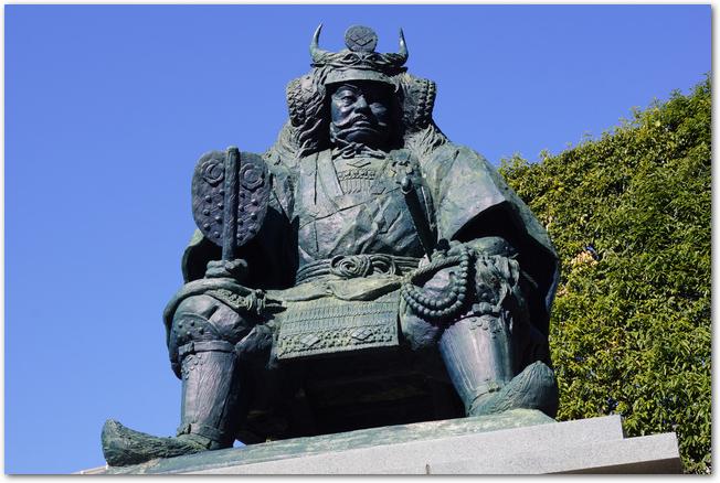 青空を背景に見上げる武田信玄の銅像