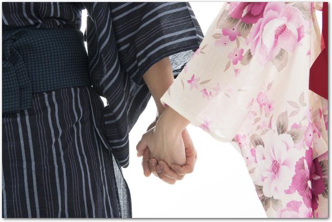 手を繋ぐ浴衣姿のカップル