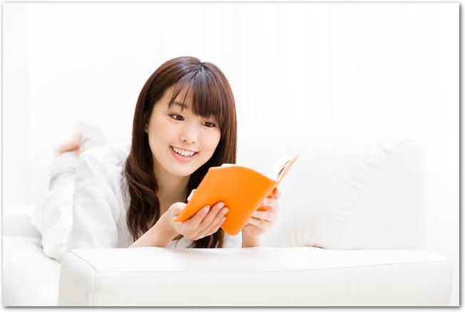 ソファーに寝転んで雑誌を読む女性の様子