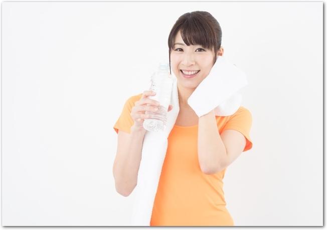 大きめの白いタオルで顔を拭く女性の様子