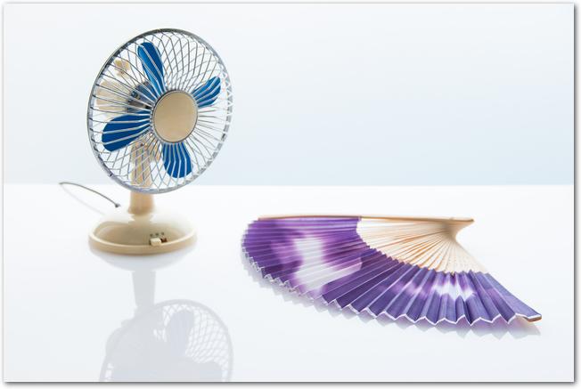 ミニチュアの扇風機と紫色の扇子
