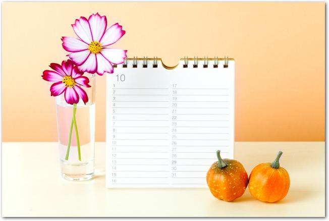 10月の卓上カレンダーとコスモスの活けられた花瓶