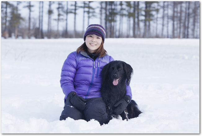 雪の中に黒い愛犬と座る女性