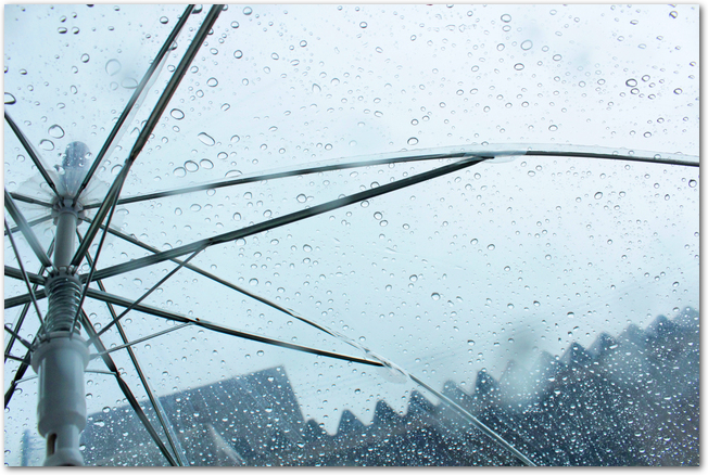 水滴がついたビニール傘ごしに見る雨の日の空