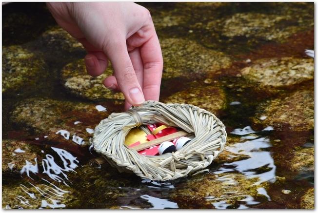 水辺に流し雛を浮かべている様子