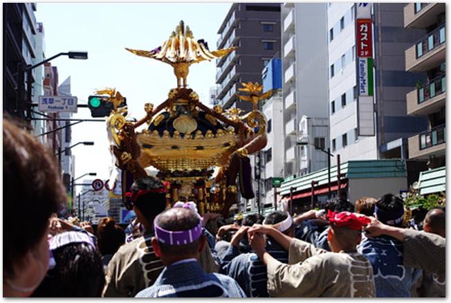 道路を三社祭の神輿が練り歩いている様子